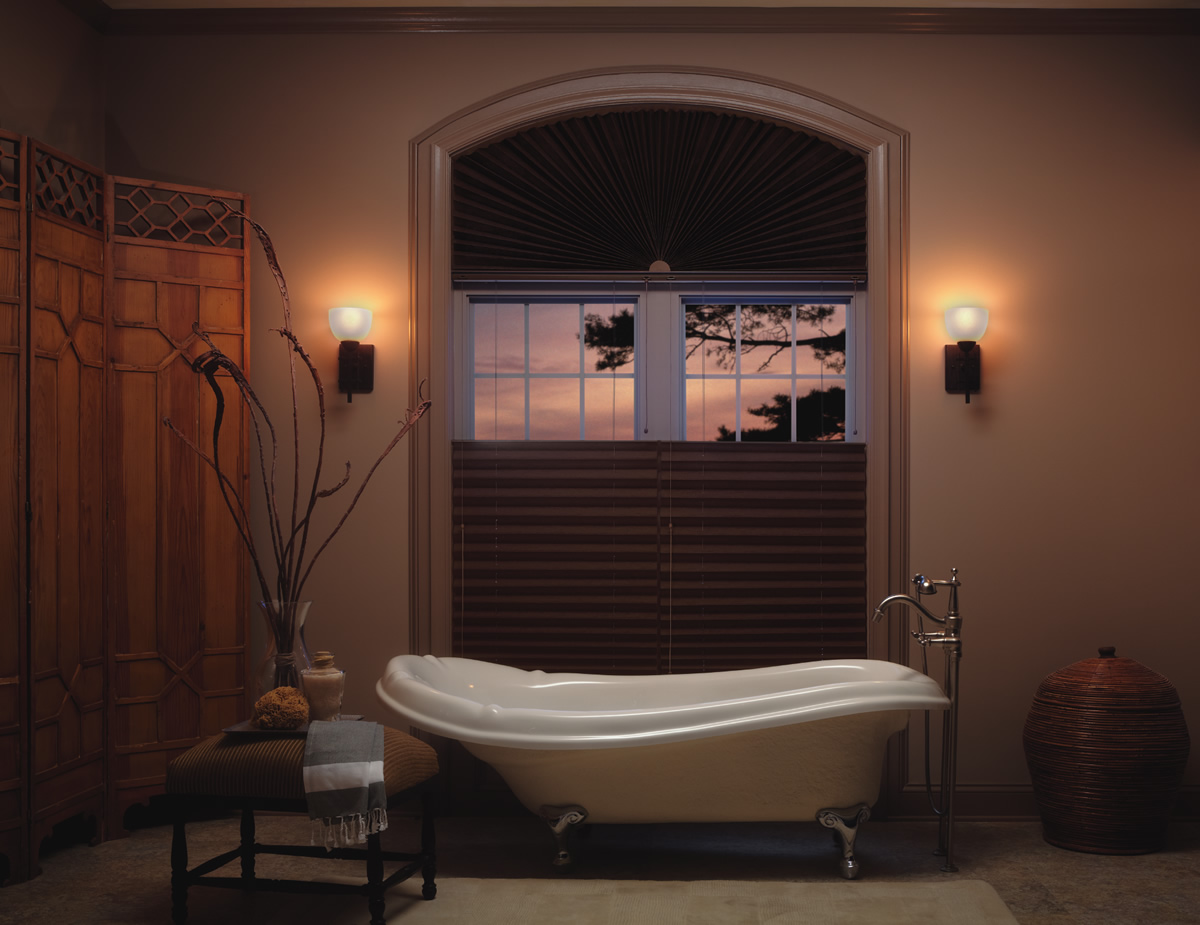 brown roman pleated shades in a bathroom window