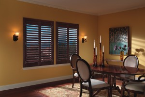 wooden window shutter installed in a yellow painted wall of a dining room