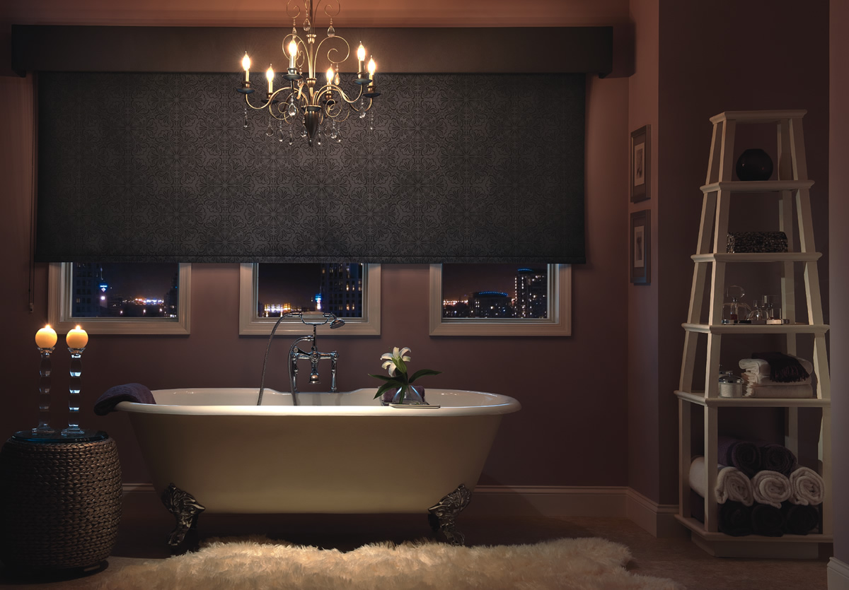 a black roller shades installed in a bathroom with a white bathtub and a chandelier on the ceiling
