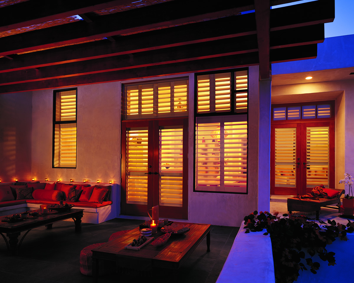 warm lit home with window shutters against an evening night sky