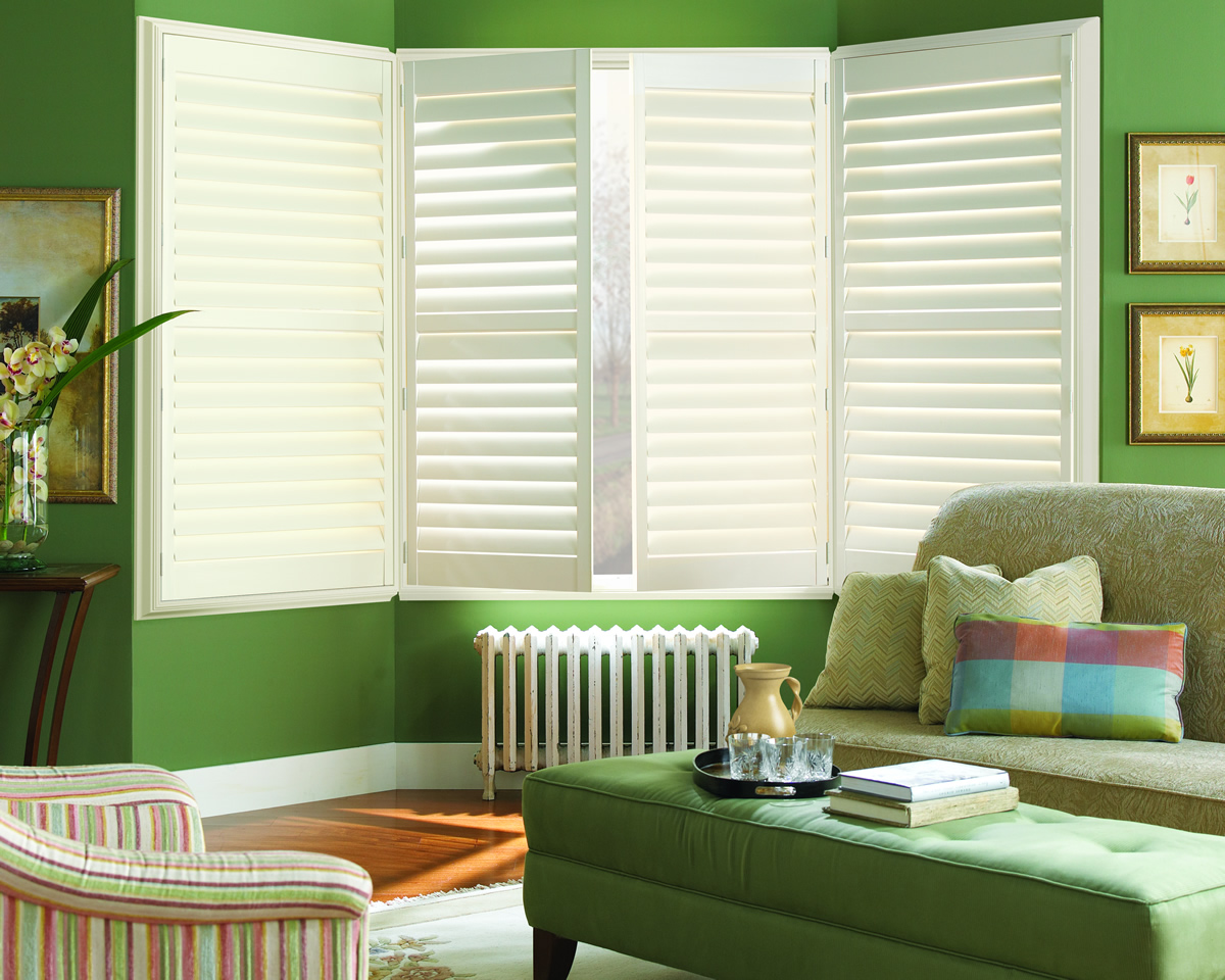 white window shutters installed in the cozy green living room