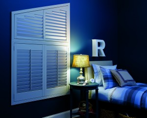 white window shutter installed in a cozy blue bedroom