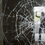 a broken wall glass and a silhouette of a person holding something