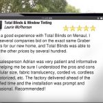 A person holding an iPad reading about a five star review of Total Blinds and Window Tinting for another job well done of installing graber blinds.