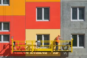 Contractor wearing a jeans, orange jacket and protective helmet is standing on a hanging high rise window cleaning lifter and installing the Window Tint UV Protection while painting halfway on the wall of a building in a red, yellow and flesh colors