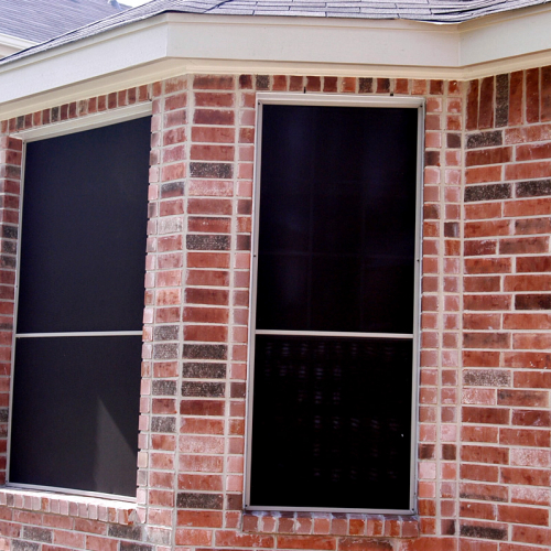 close-up view of black solar roller shades installed in the house window made of bricks
