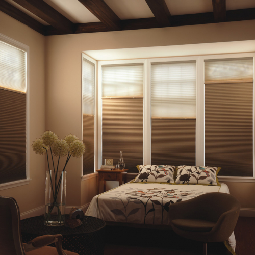 white and brown cellular shades installed in a bedroom window