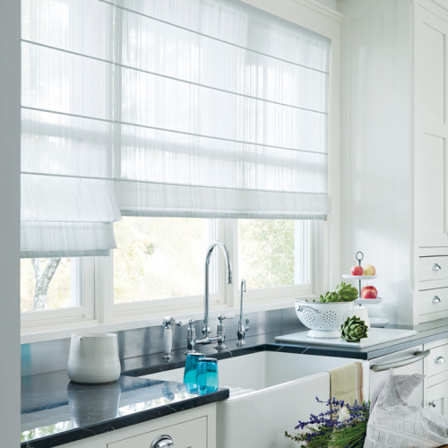 white see-through roller shades installed in the window beside the kitchen sink