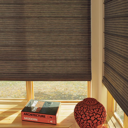 dark brown window shades installed in a glass window with architecture book below